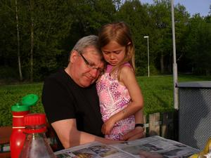 Farfar tröstar Mira som slagit sig på gungbrädan.