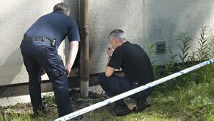 Polisens brandtekniker Erns Lindberg (sittande) och en poliskollega från Bollnäs undersöker brandplatsen.
