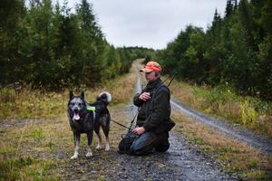 Rolf Henriksson pustar ut med sin hund efter den första rundan i skogen.
