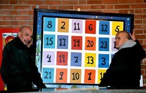 Anders Jonsson och Oskar Koskinen monterar upp Alléhallens traditionella julkalender. Det är för femte året som kalendern, som är utformad av Jan Hult, pryder väggen intill kiosken i Alléhallen.Foto: Samuel Borg