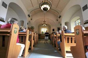Historia. Kyrkan brann 1902 och byggdes upp igen 1910 berättar guiden Ewa Wetter. Ljuskronorna kommer från NK.