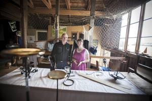 Roland Olsson, som driver Smedjan i Bleka, och hemslöjdskonsulent Susann Myrenhammar framför det dignande bordet av alster som ska utropas på hantverksauktionen. Torgny