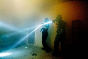 Polisaspiranterna Marie Brodin och Maria Halvarsson försöker övertala en envis figurant att komma ut ur det rökfyllda rummet med händerna på huvudet.Foto: Henrik Flygare