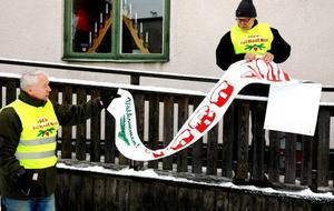 JUL JUL. Tage Elvin sätter upp en banderoll tillsammans med form- givaren Leif Högström.