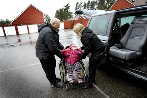 Familjen har en specialbyggd bil med lift och vridbara säten så att Alicia lätt kan placeras i baksätet. Bo Och Helena hjälps åt att lyfta in Alicia. Det regnar ute och Alicia har dragit ned mössan långt ned över ögonen.
