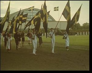 Beredskapsfest. I den film som Artur  Åslund kallar Sandvikenfilmen besöker han beredskapsfesten på Jernvallen två år  i rad. Här tågar fanbärarna in på idrottsplatsen vid 1940-års fest.