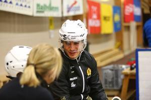 Henrik Hetta knyter skridskor tillsammans med några av ungdomarna som anmält sig till träning med Skellefteå AIK.