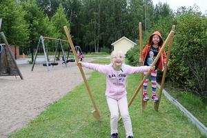 Moa Lööv och Alisia Fritz försöker lära sig att gå på styltor på skolgården.