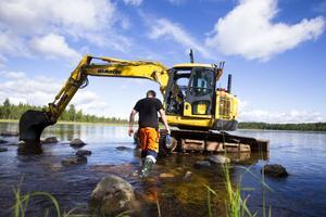 Ett härligt jobb, tycker Joel Björklund, här på väg ut till sin grävmaskin, att det vådliga arbetet i forsen är.