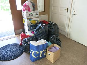 Säckar, kartonger och påsar fulla med kläder och skor.