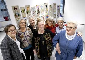 Broderigruppen Tokbrodöserna har en samlingsutställning i stadshusfoajén, och i bakgruden hänger det stora Södertäljeverket. Från vänster: Birgitta Norring, Christina Hillemar, Ulla Östlund, Margit Holmer, Ann-Katrin Larsson, Ulla Howding och Synnöve Andersson.
