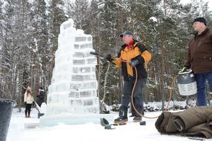 Gasolbrännare. Benny Sörensen smälter ihop isblocken och fixar till skulpturens slutfinish. Börje Horm assisterar som bärare av utrustning.