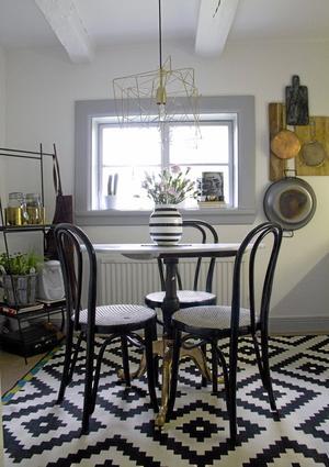 Skärbrädor och köksattiraljer blir vackra även på väggen. Stolarna är loppisfynd och bordet ett gammalt omgjort.