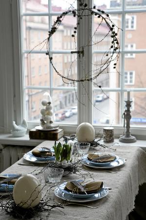 Här har naturen fått vara inspirationskälla. En fönsterkrans av lärkkvistar, ägg, fjädrar och björkris är stommen i påskdukningen.Foto: Anna Lefvert