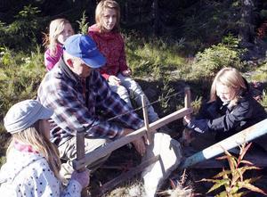 Evelina Isaksson, till vänster, och Emilia Nilsson, till höger, sågar sten vid skifferbrottet. Jan-Åke Karlsson håller i stenen och bakom sitter Amanda Nilsson och Jennifer Henriksson.