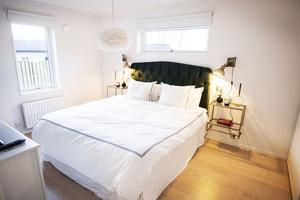 Det är många olika typer av fönster i huset. Sänggaveln i grön sammet är köpt på nätet.