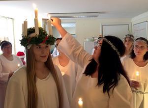 Maria Nordin har redan klarat av sitt luciauppdrag. Nu tänder hon ljusen på Amanda Andersson huvud. Nästa gång är det Anna Arneséns tur, hon kollar in ritualen i högerkant.