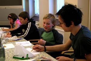 Serietecknande. Mattias Holding närmast instruerar Carl Brandt i mangatecknandets olika tekniker