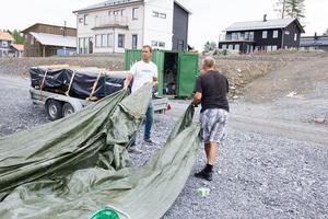 Robert Brandt och hans pappa Krister Brandt tar bort presenningen från det blivande garagegolvet.