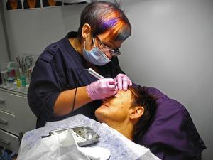 Leena Elingsbo unför här en kosmetisk tatueringbehandling på en besökare.