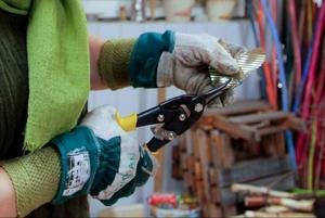 Susann Jarlsdotter Myrenhammar klipper till en bit plåt av en gammal champinjonburk.