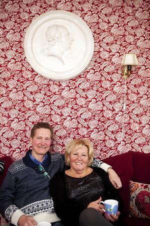 Förmaket/Vardagsrummet. Jan och Leea sitter i soffan under en porträttmedaljong, som Jan köpt på auktion. Tygtapeten är från Ikeas 1700-tals kollektion, lampetterna hade Leea med sig till boet.