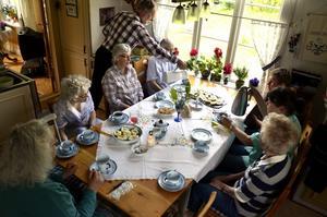 Kaffetåren. Runt bordet sitter föreningens kvinnor som blir serverade nybryggt kaffe av Asta Nilssons son Kjell.