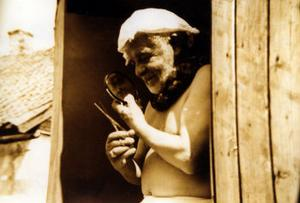 Evert Taube putsar och ansar sitt skägg efter morgondoppet på Gotland sommaren 1955.