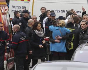 Människor utanför tidningsredaktionen i Paris där minst tolv människor miste livet i Frankrikes hittills blodigaste terrorattentat.