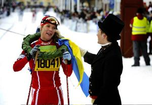 Sandra Hansson gratuleras av kransmasen Jonas Nilsson.
