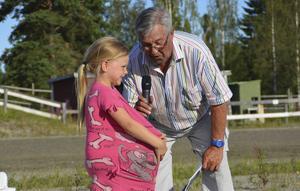 Speakern Lennart Hobring och lilla Tova i segerintervju. Tovas mamma Linda Fastesson vann två lopp och blev årets kuskchampion.