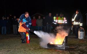 Unge Daniel Hed får hjälp av pappa Lars-Erik att släcka en öppen eld med en pulverbrandsläckare.