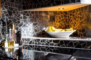 Köket i ek och med bänkskiva i granit är mörkare än köket i huset. Det har påverkat stilen i övriga lägenheten.