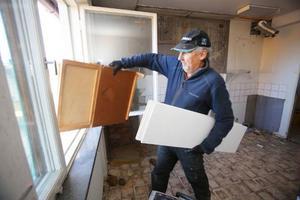 Gunnar Petersson skickar ut gamla skåpluckor ut genom fönstret till den väntande sopcontainern nedanför.