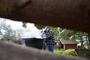 Varmt vid grytan. Lennart Sandberg kokar vidjor av gran till hembygdsföreningens gärdesgård. Man har också använt ståltråd att binda ihop störar med vid gärdesgårdsbyggande, men det traditionella sättet är att bara använda naturmaterial.