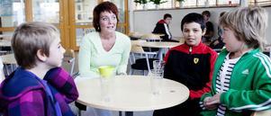 Fjärdeklassarna Samuel Stenberg, Rasmus Svärdström och Philip Andersson fikar med sin lärare Eva Zetterman. De dricker saft, hon gratiskaffe.