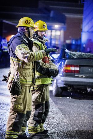 Arja Babamiri (t h) får instruktiner av en brandman om hur han ska agera under räddningsarbetet.