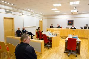 Mannen som misstänks för två mordförsök i Högbo övervakas av tre män från Kriminalvården, till vänster. Rådman Hans Holback är rättens ordförande.