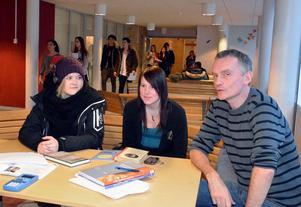 Ekonomistuderande Elise Tollsten och Erika Wengelin pratar skola med klassföreståndaren Henrik Åberg.