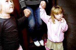HÅLLER I FARMOR. Tyra Linnér, 5 år och Freja Linnér, 4 år håller farmor i handen mellan spöken och tågvagnar.