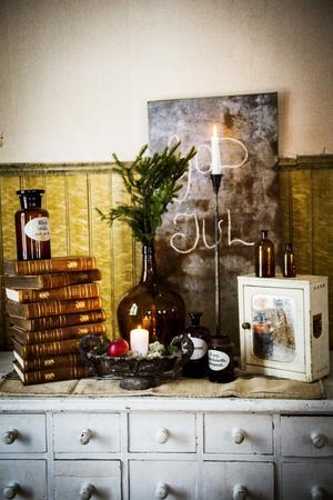 En gammal köpmansdisk har pyntats med gamla böcker, flaskor material från naturen.