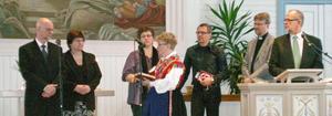 Det nya pastorsparet Tord och Evabritt Johansson, till vänster, välkomnas av bland andra sockenklädda Ingrid Sammils.