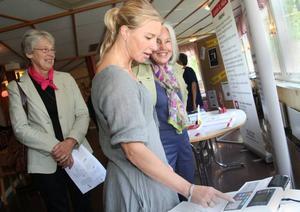 Ulrika Olsson från Folkhälsoenheten mäter Maud Larssons fettprocent i förhållande till kroppsvikten. Margareta Ehn väntade på sin tur.