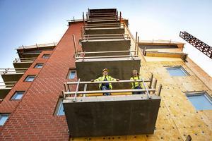 Snickarna Andreas Modin och Lars-Åke Henriksson hänger på en av balkongerna som ska glasas in.