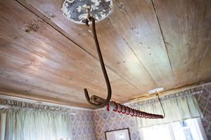 I taket i storstugan satt två metallfästen och av en vän som är antikhandlare fick de två krokar och en brödstång som passade perfekt