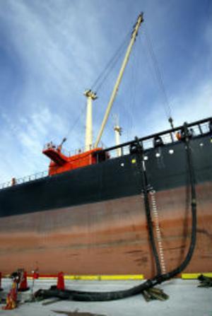 Eldningsoljan togs ombord i Libyen och slangas nu ner i lagerrum för att sedan användas i Korstaverken.