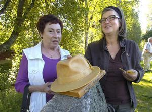 Konstnären Katharina Jönsson Norling till höger visar Hans Lidmans dotter Carin Lindbäck hur utsmyckningen kommer att se ut. Hans Lidmans karaktäristiska hatt ovanpå en bok på toppen av stenen som i övrigt är tom.