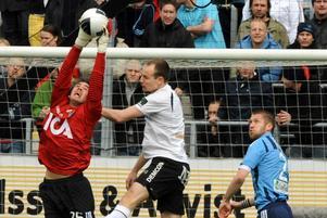 Djurgårdens målvakt Tommi Vaiho sträcker sig och tar bollen framför Örebros Kim Olsen.