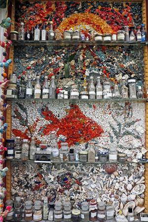 Ingalill samlar på sand från olika delar av världen. Hennes mamma var konstnär och har smyckat väggen bakom.