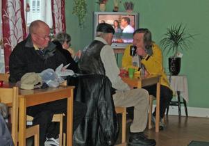 Sture Pettersson har just börjat öppna sin julklapp och i bakgrunden Birgitta och Bernt Andersson samt Håkan Hallin.